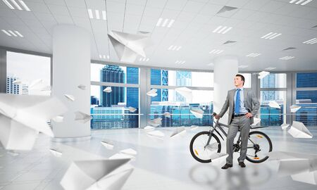 Confident and successful man wearing business suit and tie with bike at comfortable coworking space with flying paper planes. Businessman relaxing with bicycle at modern office with big windows. Zdjęcie Seryjne