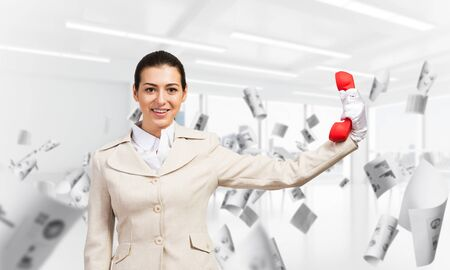 Woman keep at distance vintage red phone. Elegant operator in white business suit posing with landline phone in office with flying paper documents. Hotline telemarketing and business communication. Banco de Imagens