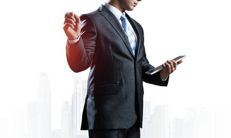 Business advisor standing and pointing copy space. Business presentation and marketing. Man in formal wear on background foggy cityscape. Financial specialist with raised hand promotion mockup Stockfoto