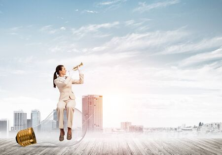 Attractive woman playing trumpet brass on background modern city and storming sky. Young businesslady in white suit sitting on big light bulb with music instrument. Musician practicing and performing