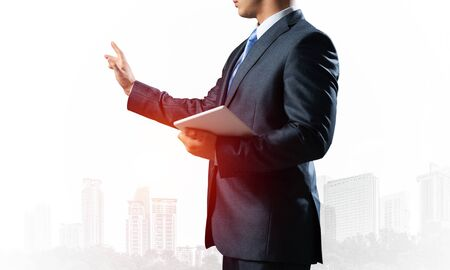Business expert standing and pointing copy space. Accounting and consulting. Side view of man in formal wear on background foggy cityscape. Financial specialist with raised hand promotion mockup.