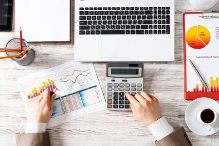 Businessman using calculator at wooden desk. Financial audit and finance accounting. Top view office workplace with man hands calculating balance. Flat lay table with laptop and business charts.