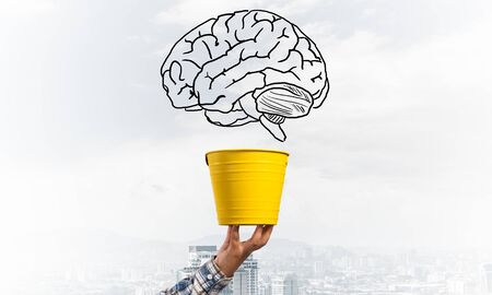 Brain drawing flying above yellow pot. Human hand holding pot with brain on modern cityscape background. Brainstorming and creative idea generation. Business education and knowledge. 스톡 콘텐츠