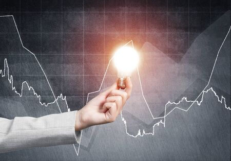 Businesswoman holding glowing light bulb on grunge background with financial diagram. Competent business data analysis. Idea generation and brainstorming. Successful solution concept with lamp.