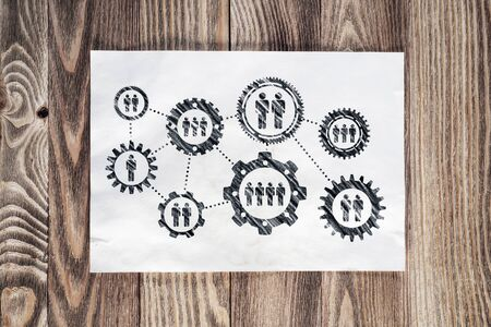 Human resource recruitment pencil hand drawn with group of rotating cogwheels. Headhunting and team building sketch on wooden surface. Top view of workplace with sheet of paper lying on wooden desk.