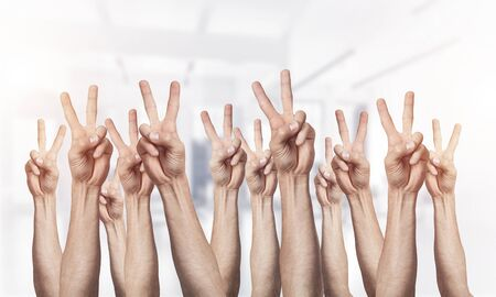Row of man hands showing victory gesture. Winning or triumph group of signs. Human hands gesturing on light blurred background. Many arms raised together and present popular gesture.