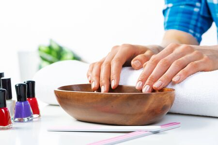 Closeup female hands in wooden bowl with water. Spa procedure and relaxation. Female hands preparing for manicure. Professional nail care and beautician service. Beauty and hygiene concept