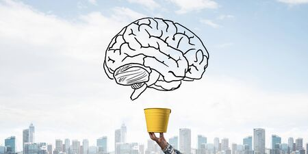Brain drawing flying above yellow pot. Human hand holding pot with brain on modern cityscape background. Brainstorming and creative idea generation. Business education and knowledge. Stok Fotoğraf