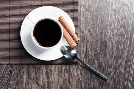 Cup of espresso coffee on wooden table. Top view white porcelain cup and cinnamon sticks on saucer. Close up fresh and aromatic hot drink in cafe. Morning coffee and break time concept. 写真素材