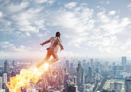 Businessman in suit and aviator hat flying in blue sky as superhero Stok Fotoğraf