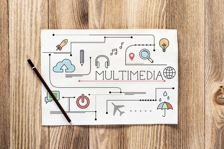 Multimedia content pencil hand drawn with group of social media doodles. Top view of workplace with paper and pencil lying on wooden desk. Commercial marketing and business presentation. Banco de Imagens