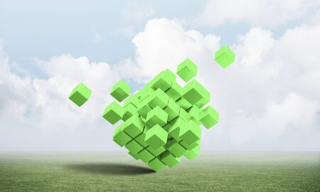 Abstract green cubes on green meadow. Digital technology and innovation solutions. New approach to business management. Nature landscape with green grass and blue sky. Mixed media with 3D object 写真素材