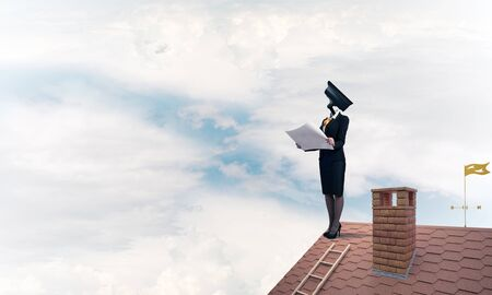 Faceless businesswoman with camera zoom instead of head standing on house roof Imagens