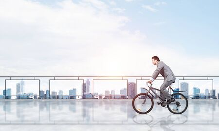 Man wearing business suit riding bicycle on penthouse balcony. Handsome cyclist on background of city center architecture. Terrace with modern downtown view. Real estate agency business concept