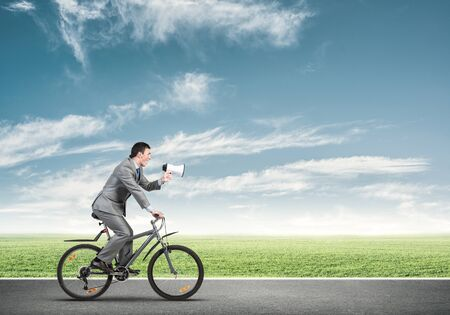 Businessman with megaphone on bike at sunny day. Marketing and advertising campaign. Manager in business suit riding bicycle and speaking in loudspeaker. Cyclist on background green grass and blue sky
