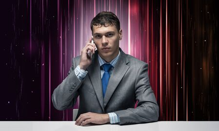 Internet consultant talking on phone. Businessman sitting at desk on abstract matrix like background. Portrait of hosting service manager wears business suit and tie. Internet consulting and marketing Imagens