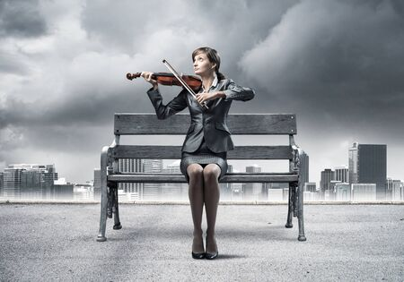Young woman with violin sitting on wooden bench. Attractive businesslady playing violin on background modern cityline panorama with cloudy storm sky. Musician practicing and performing outdoors.