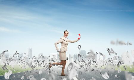 Woman running outdoor with vintage red phone. Expressive secretary with telephone and flying various letters around. Hotline telemarketing and communication. Professional business assistance Banco de Imagens