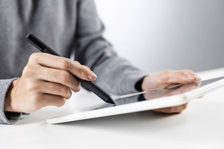 Businesswoman using tablet computer for news read. Close-up of female hands holding tablet device at office desk. Online business statistics and analytics. Modern workplace in innovate company 免版税图像