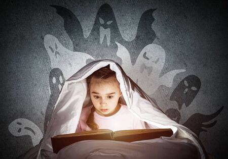 Scared little girl reading fairytales in bed. Child with flashlight hiding under blanket. Kid can not sleep at night. Girl in pajamas and frightening ghosts back on wall. Halloween holiday concept