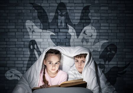 Cute girl and boy reading kids book in bed. Children with flashlight lying under blanket together. Kids in pajamas and funny ghosts silhouettes back on grey wall. Children reading magic fairy tales