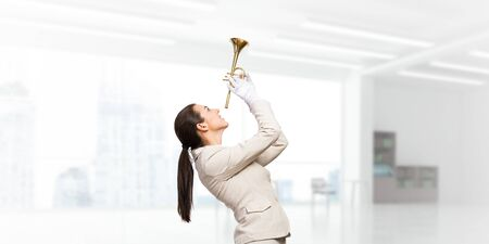 Beautiful woman holding trumpet brass overhead. Young smiling businesslady in white business suit and gloves posing with music instrument in light office interior. Business concept with musician Stock Photo