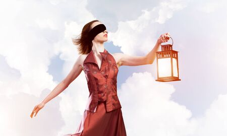 Young woman wearing blindfold with lantern against cloudy sky
