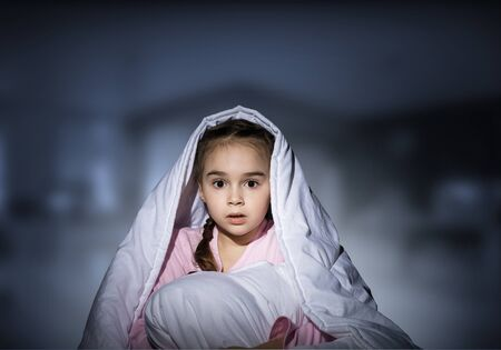 Scared girl with pillow hiding under blanket. Startled kid lying in his bed at home. Little girl afraid of dark. Covered child not sleep at night. Girl in pajamas on deep blue blurred background