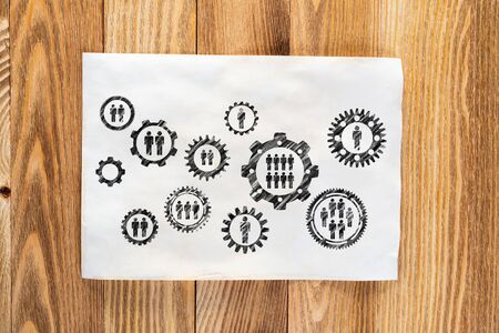 Business process management pencil hand drawn with group of rotating cogwheels. Human resources sketch on wooden desk. Workplace with sheet of paper on wooden desk. Social communication infographics