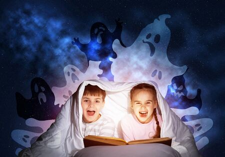 Happy little kids reading magic fairy tales in bed. Brother and sister together hiding under blanket. Little friends in pajamas with open big book and imaginary monsters on deep blue background. Stockfoto