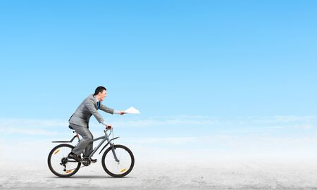 Businessman with paper documents in hand on bike. Deadline for paperwork. Corporate employee in grey business suit riding bicycle on background of skyscape. Accounting and financial statements Archivio Fotografico