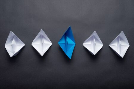 Row of paper ships on black background. Leadership concept with blue paper ship leading among white. Individual motivation and direction. Social marketing layout with copy space.
