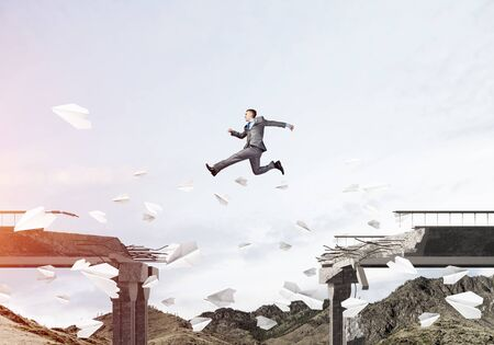 Businessman jumping over gap in bridge among flying paper planes as symbol of overcoming challenges. Skyscape with sunlight and nature view on background. 3D rendering. Stok Fotoğraf