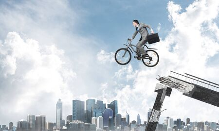 Man on bike jumping from broken bridge. Businessman on bike hurry to work. Corporate employee in business suit with suitcase on cycle flying in air. Cyclist on background modern cityscape and blue sky