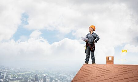 Builder in hardhat with technical blueprints. Young female architect in shirt and jeans standing on brick roof of house. Professional success and new horizons. Renovation and roofing construction.