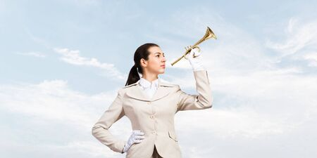 Beautiful woman playing trumpet brass. Young businesslady in white business suit and gloves posing with music instrument on blue sky background. Harmony and creativity in business.