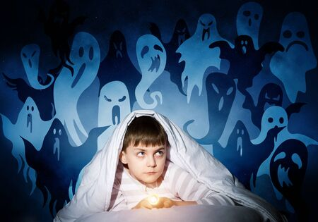 Scared boy with flashlight hiding under blanket. Startled kid lying in his bed at home. Little boy afraid of dark. Fearful child in pajamas and imaginary monsters. Halloween holiday concept