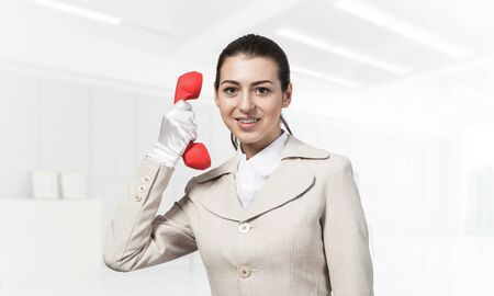Smiling young woman holding retro red phone. Call center operator in white business suit posing with telephone in light office interior. Hotline telemarketing. Business assistance and consultation. Фото со стока