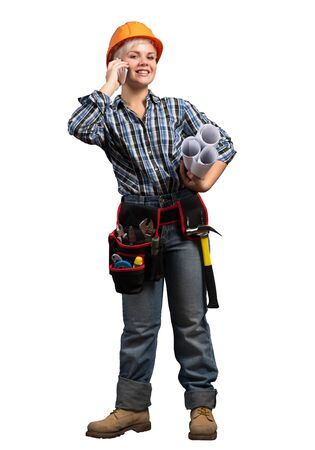 Attractive blonde woman in workwear and hardhat talking on smartphone. Young engineer in checkered blue shirt and jeans isolated on white background. Business communication and conversation.