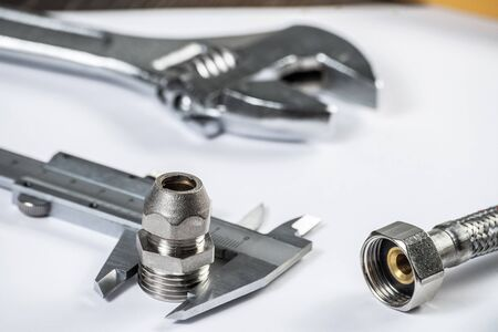 Water braided metal hose with connecting internal screw. House hydraulic system construction and engineering. Plumbing pipeline and caliper laying on table. Bathroom repair or construction service. Stock Photo