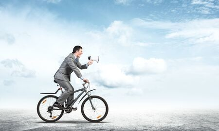 Businessman with megaphone on bike at sunny day. Marketing and advertising campaign. Manager in business suit riding bicycle and speaking in loudspeaker. Male cyclist on background of blue sky. Imagens