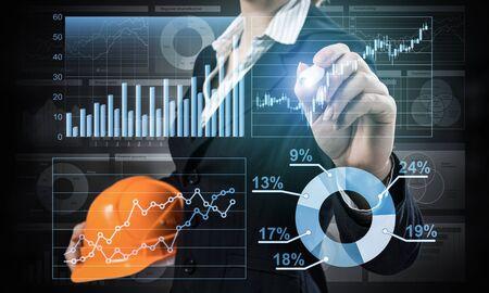 Empresaria apuntando en gráfico financiero 3d. Mujer en traje de negocios de pie con casco de seguridad. Tecnología digital e innovación en la industria de la construcción. Visualización de datos de economía e inversión.