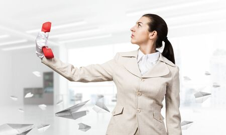Woman keep at distance vintage red phone. Elegant operator in white business suit posing with landline phonein office with flying paper planes. Hotline telemarketing and business communication.