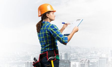 Young building controller with clipboard standing and filling examination report. Side view of woman construction specialist in workwear and hardhat writing in checklist. Professional house audit