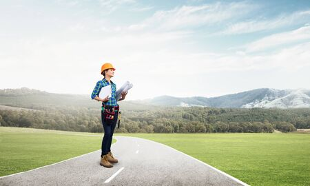 Young woman in safety helmet standing on asphalt highway with blueprint. Architect in workwear checking work progress on background nature landscape. Road infrastructure reconstruction and development