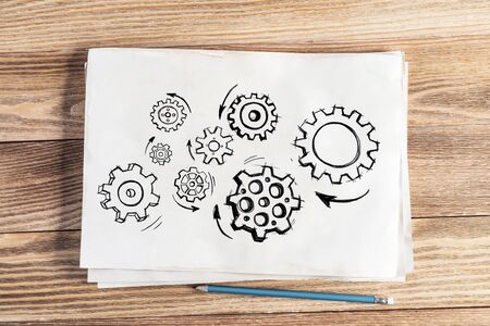 Gear wheels pencil hand drawn. Industry mechanism with cogwheels sketch on wooden surface. Artist workplace with sheet of paper and pencil lying on wooden desk. Textured natural wooden background