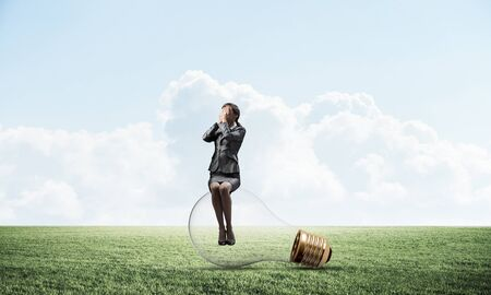 Young woman sitting on big light bulb. Girl in business suit keeps hands on face for surprise. Businesswoman playing hide and seek on green meadow. Hide from problems. Help and successful solutions