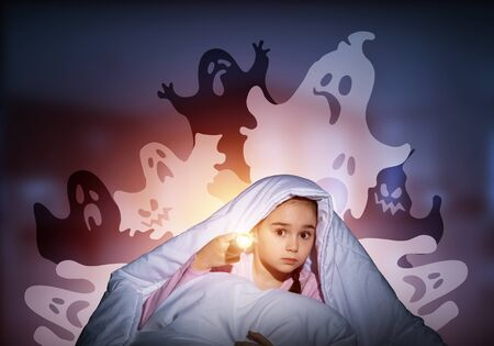 Scared girl with flashlight hiding under blanket from imaginary ghosts. Kid sitting in bed on night sky background. Covered child in pajamas not sleep at night. Mysterious phantoms in darkness. Reklamní fotografie