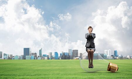 Young woman sitting on big light bulb. Girl in business suit keeps hands on face for surprise. Businesswoman playing hide and seek on background of modern downtown. Problem and successful solution