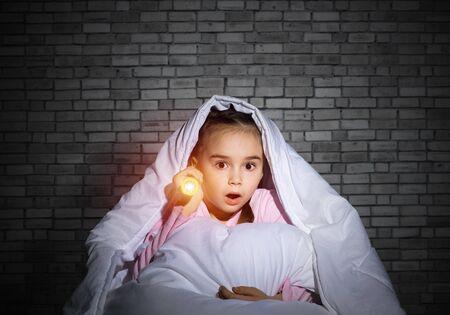 Frightened girl with flashlight hiding under blanket.